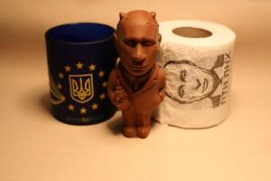 Souvenirs fra Vestukraine bestående af et krus med EU flag på, samt en chokoladefigure af Putin og en toiletrulle med Putinbilleder.