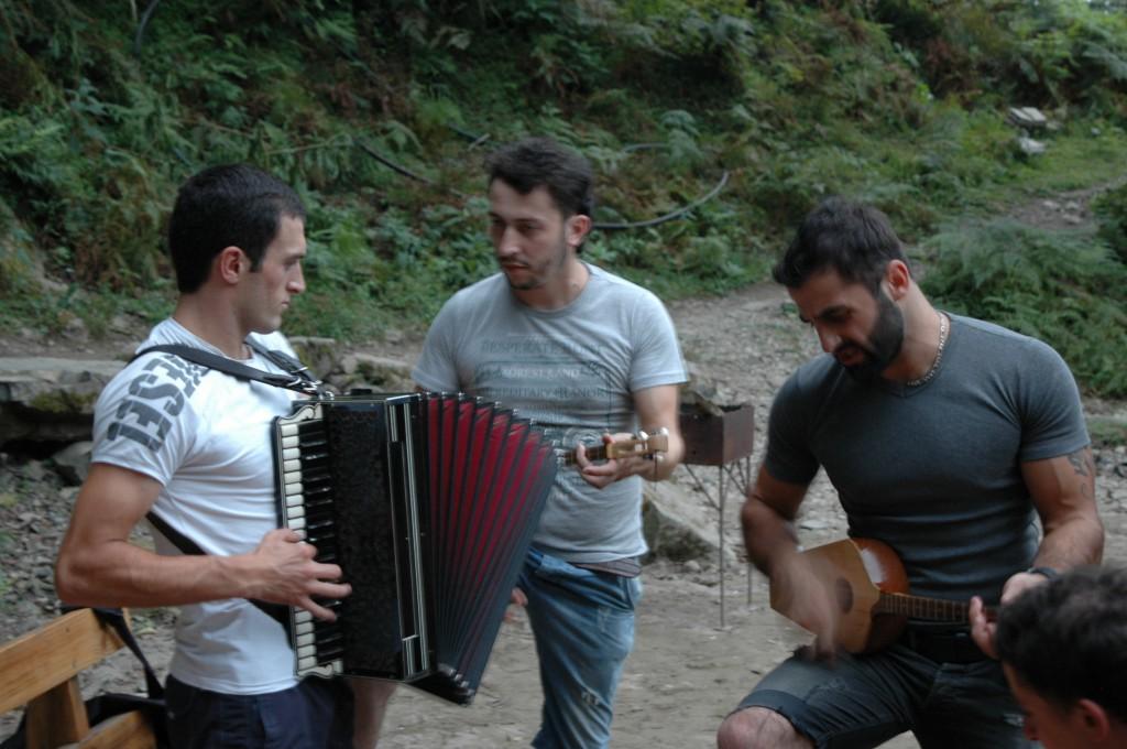 """""""Den harmonika er mere værd end hans bil"""". Rolandi Nakaidze, Gizo Abuladze og Djaba Abuladze spiller georgisk, tjetjensk, tjerkessisk og russisk folkemusik på flodbredden. Foto: Jesper Hasseriis Gormsen."""