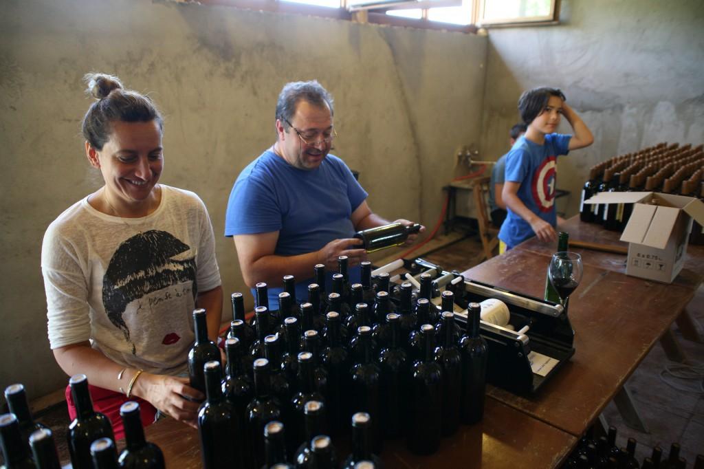 Nina Abkhaladze og Beka Gotsadze og en af deres sønner i færd med at sætte mærkater på 2000 flasker rødvin til det amerikanske marked. Foto: Anders Skærlund Petersen.