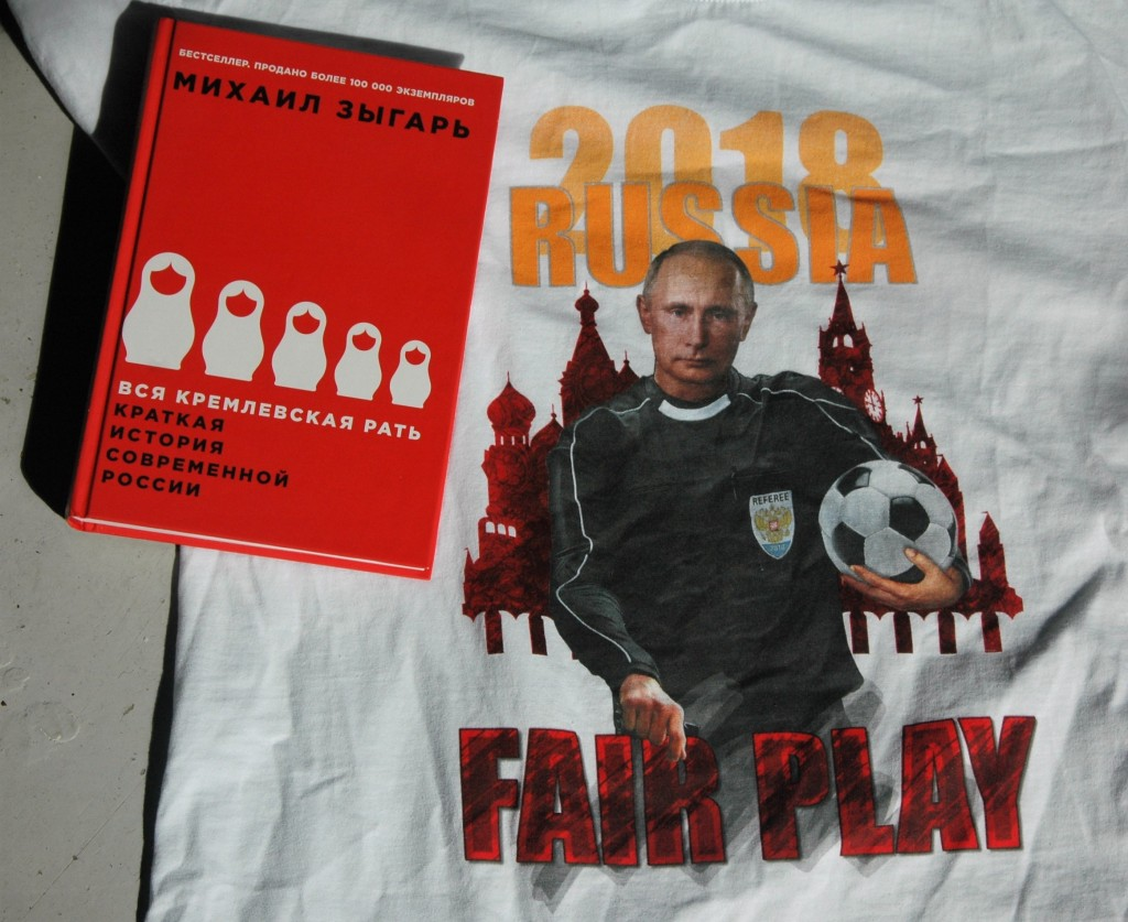 "En joke eller ramme alvor? En souvenir-t-shirt fra Sheremetyevo lufthavn udenfor Moskva. Tv. Mikhail Zygars bog ""Alle kremls mænd"". Foto: Jesper Hasseriis Gormsen."