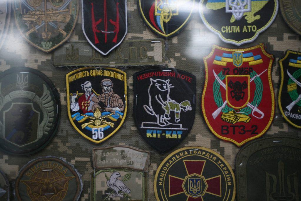 Nogle af de mange emblemer, der hænger til skue i ventesalen i Dnipro. Foto: Anders Skærlund Petersen.