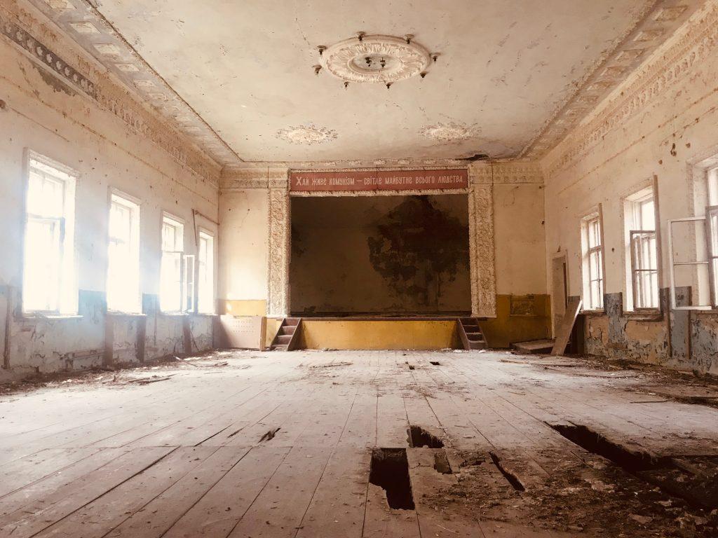 """""""Længe leve kommunismen - en lys fremtid for hele menneskeheden."""" står der på ukrainsk i et kulturhus der ligger indenfor Chernobyls eksklusionszone. HBO-serien Chernobyl viser en markant mere dyster side af kommunismen i Sovjetunionen. Foto: Julia Samokhvalova."""